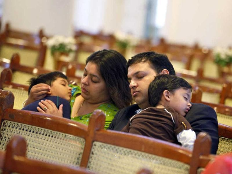 An Indian Christian family falls asleep while attending an early morning Easter Mass in Bangalore. AP