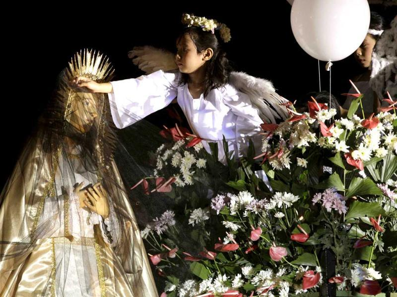 A Filipino girl acting as an angel removes the black veil of