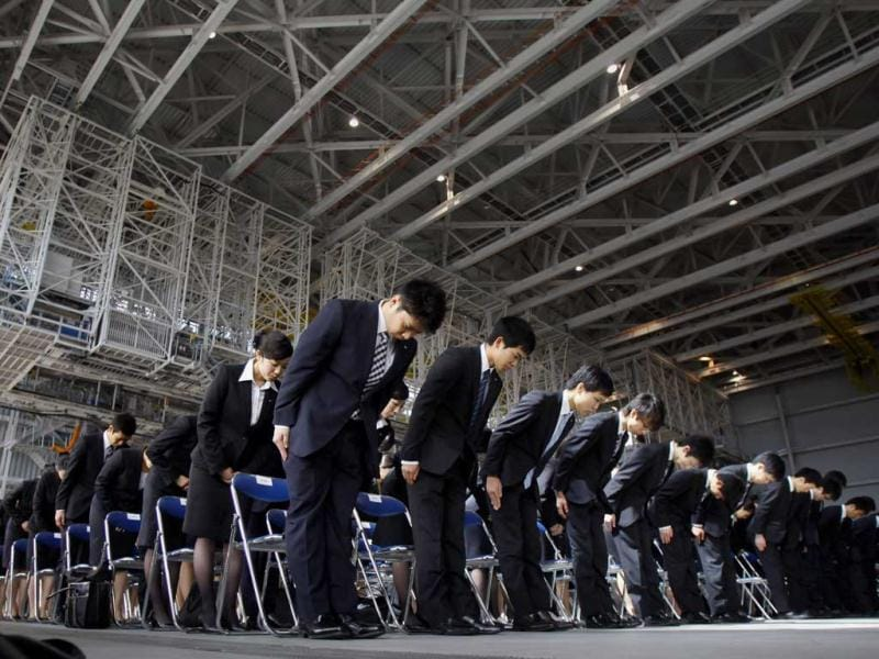 Newly hired employees of All Nippon Airways and ANA group companies bow during an initiation ceremony at the company's aircraft maintenance hangar in Haneda airport in Tokyo. A total 1,068 new recruits attended the ceremony, according to the company. (AP)