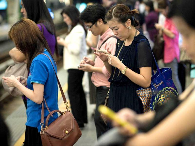 People use their smartphones while waiting for a train in Bangkok. A recent Facebook-sponsored study shows smartphone owners are often connected all day. People can be found glued to their smartphones even while crossing the street, creating a disconnect with their immediate surroundings. AFP Photo