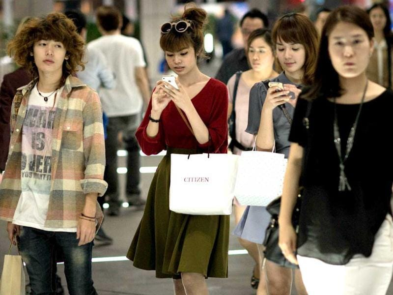 Women walk while using their smartphones in Bangkok. A recent Facebook-sponsored study shows smartphone owners are often connected all day. People can be found glued to their smartphones at airports, on trains, in restaurants and even while crossing the street, creating a disconnect with their immediate surroundings. AFP Photo