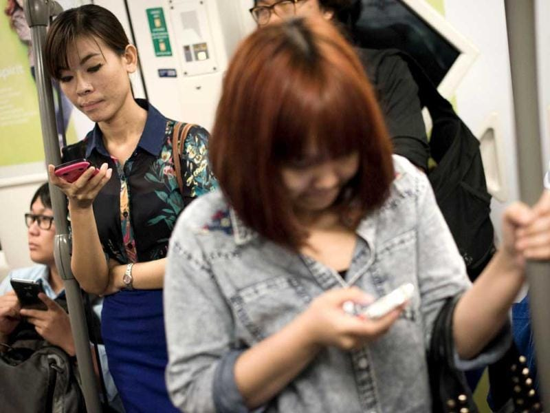 People use their smartphones to stay in touch with friends, family and colleagues on a BTS train in Bangkok. A recent Facebook-sponsored study shows smartphone owners are often connected all day. People can be found glued to their smartphones even while crossing the street, creating a disconnect with their immediate surroundings. AFP Photo