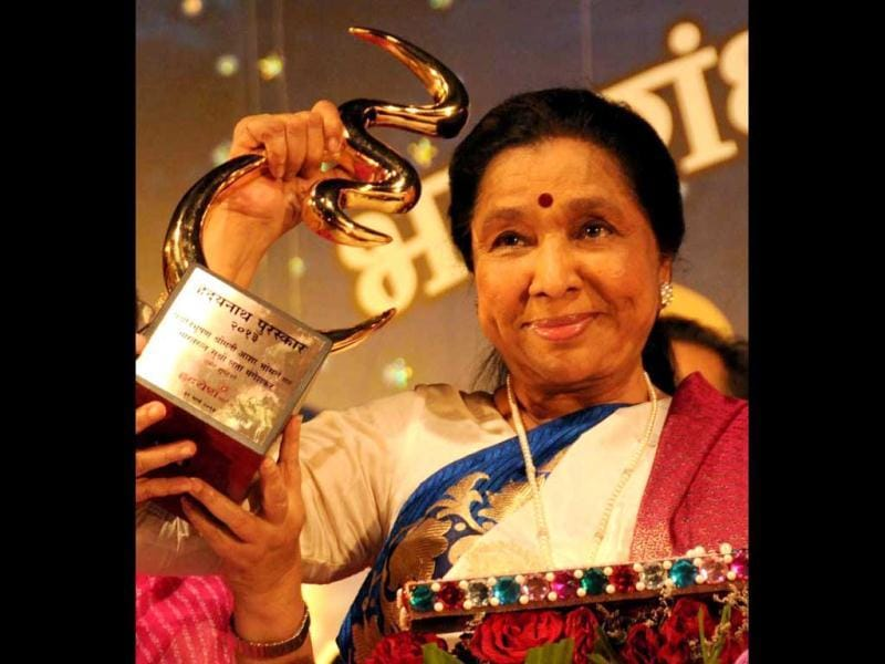 Singer Asha Bhosle holds up her statuette after being felicitated in Mumbai on Sunday night. (PTI Photo)