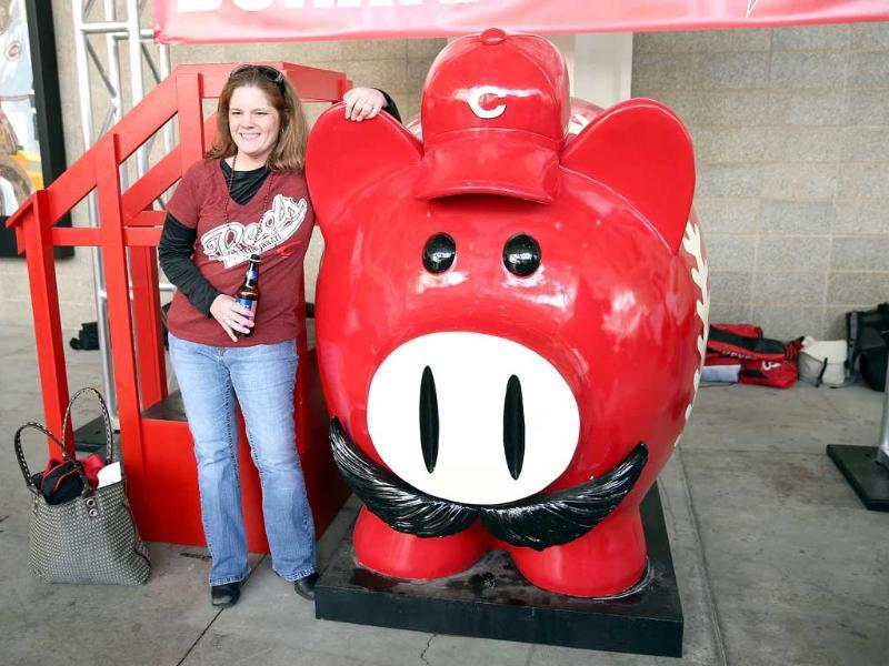 Amy Venable poses with a large piggy bank before the start of the Los Angeles Angels of Anaheim game against the Cincinnati Reds at Great American Ball Park in Cincinnati, Ohio. AFP