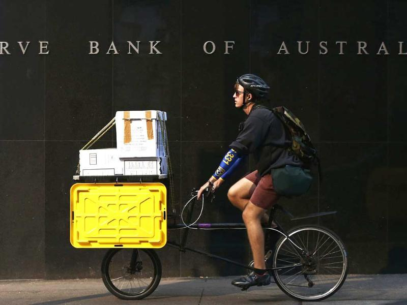 A worker on his bike rides past the Reserve Bank of Australia building in central Sydney. Reuters