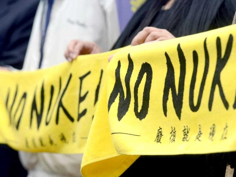 Representives anti-nuclear power plant groups display banners outside the cabinet office before a meeting with Premier Jiang Yi-huah in Taipei. (AFP)
