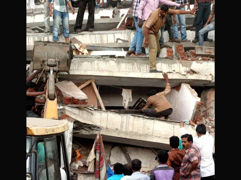 Rescuers look for survivors in the debris of the building. The seven-storey building in Shil Dhaigar locality was unauthorised, civic officials said, adding that it was occupied up to at least the fourth floor. PTI