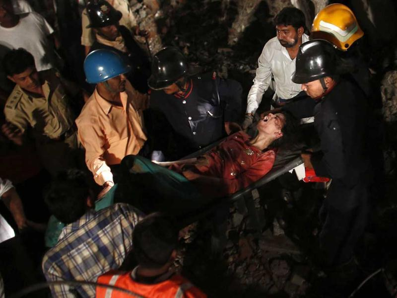Rescuers carry a survivor from what was left of a Thane building that collapsed at 6:30 pm on Thursday. They expect to find more injured trapped within the pile of debris. (Reuters)
