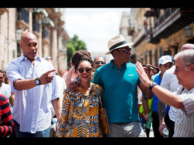 Beyonce, Jay-Z right, tours Old Havana as a body guard, left, and tour guide, right, accompany them in Cuba. (AP Photo)