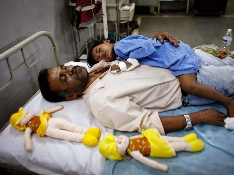 A girl who was injured during the collapse of a residential building, rests with a social worker on a hospital bed in Thane district, on the outskirts of Mumbai. (Reuters)