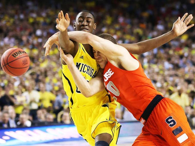Brandon Triche of the Syracuse Orange loses the ball as he drives in the second half against Caris LeVert of the Michigan Wolverines during the 2013 NCAA Men's Final Four Semifinal at the Georgia Dome in Atlanta, Georgia. AFP