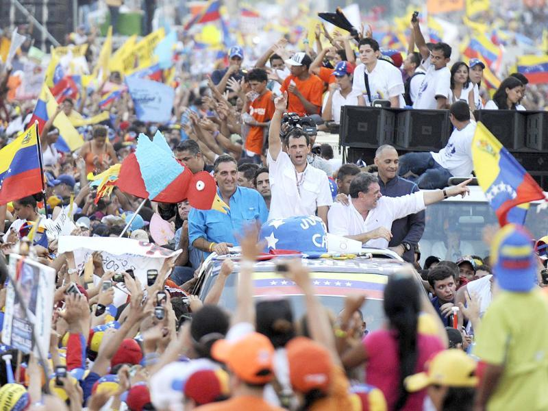 Venezuelan opposition presidential candidate Henrique Capriles greets supporters during a campaign rally in Valencia, in Venezuela. The final stretch of Venezuela's race to replace Hugo Chavez coincides with a delicate anniversary for the opposition: 11 years since a brief coup against the late leftist leader. (AFP)