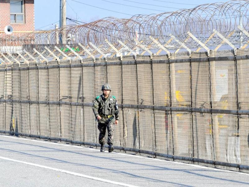 A South Korean soldier walks along a military fence on the road leading to North Korea at a military checkpoint in the border city of Paju. South Korea and the United States upgraded their coordinated military surveillance status, a report said, ahead of an expected mid-range missile launch by North Korea. AFP photo