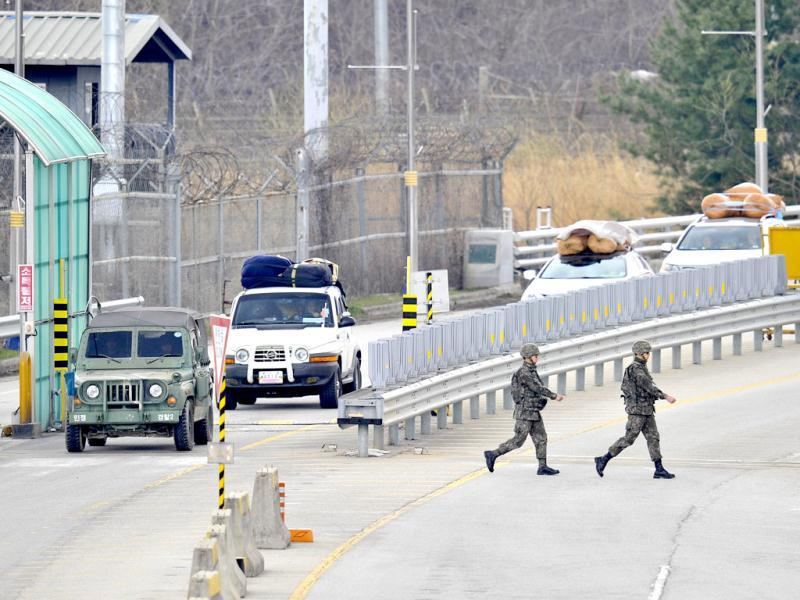 A South Korean military vehicle (L) escorts cars arriving from North Korea's Kaesong joint industrial complex, at a military check point of the inter-Korean transit office in the border city of Paju. South Korean and US forces raised their alert status to