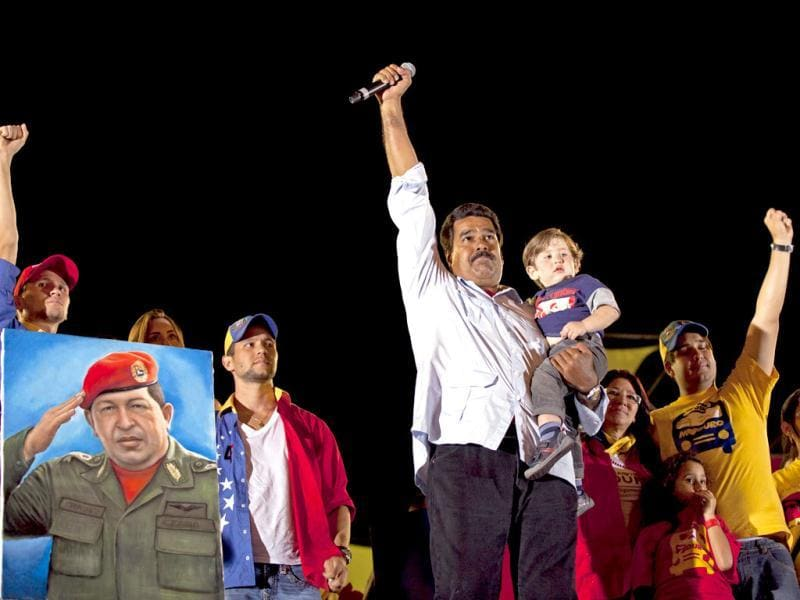 Venezuela's acting President Nicolas Maduro holds his grandson as he stands with his family on stage during his closing campaign rally in Caracas, Venezuela. (AP Photo)