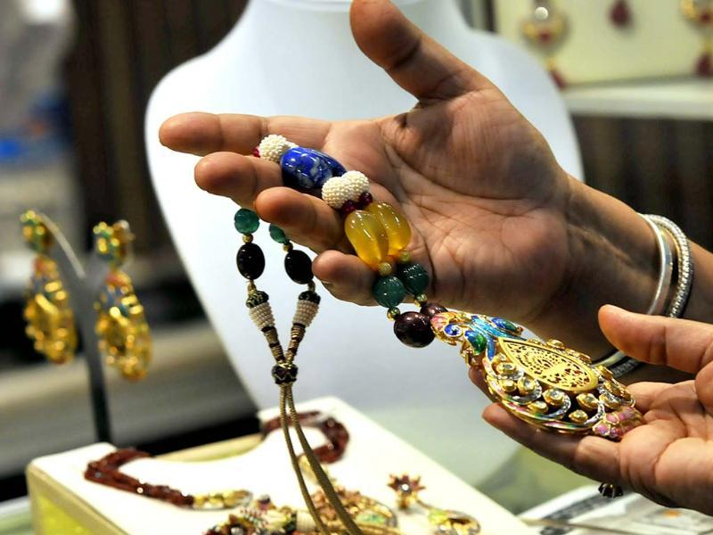 Visitors at an exhibitor's stall during the Gem and Jewellery Fair in New Delhi. HT Photo/Vipin Kumar