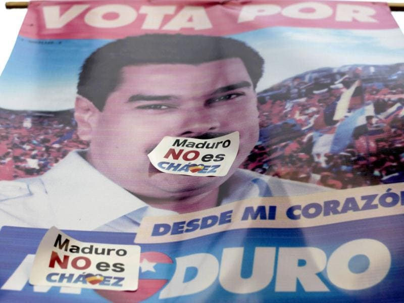 A poster featuring interim President Nicolas Maduro is covered by two small stickers that read