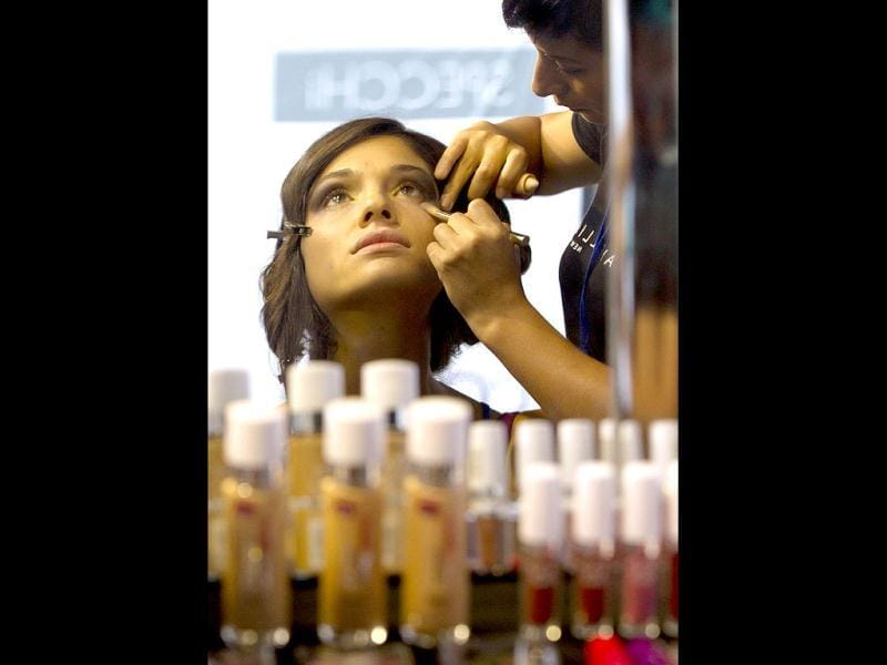 A stylist applies make-up to a model backstage prior to a show during Lima Fashion Week in Lima, Peru. (AP Photo)