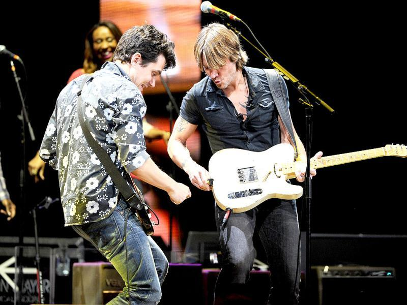Musician John Mayer, left, helps Keith Urban when his guitar strap malfunctions during their performance together at Eric Clapton's Crossroads Guitar Festival 2013 at Madison Square Garden in New York. AP Photo
