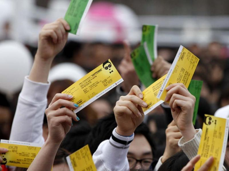 Fans of South Korean rapper Psy hold up their concert tickets as they wait in line at the Seoul World Cup stadium, the venue for Psy's concert 'Happening' in Seoul where he performed 'Gentleman' for the first time. Reuters photo