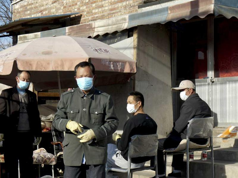 Chinese men stand guard in front of the house of a seven-year-old H7N9 bird flu patient in Gucheng village on the outskirts of Beijing. AP