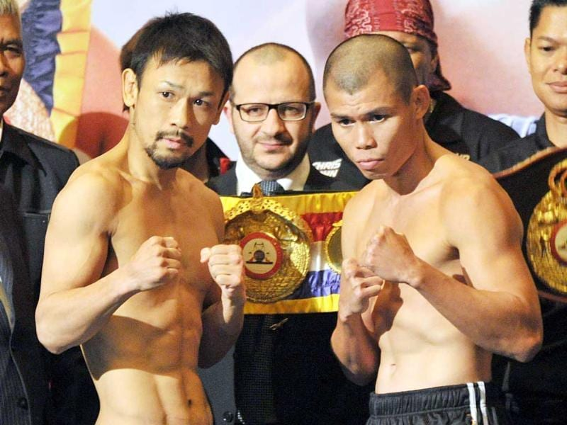 WBA featherweight champion Chris John of Indonesia and Sahoshi Hosono of Japan pose for photographers after their weigh-in in Jakarta. AFP