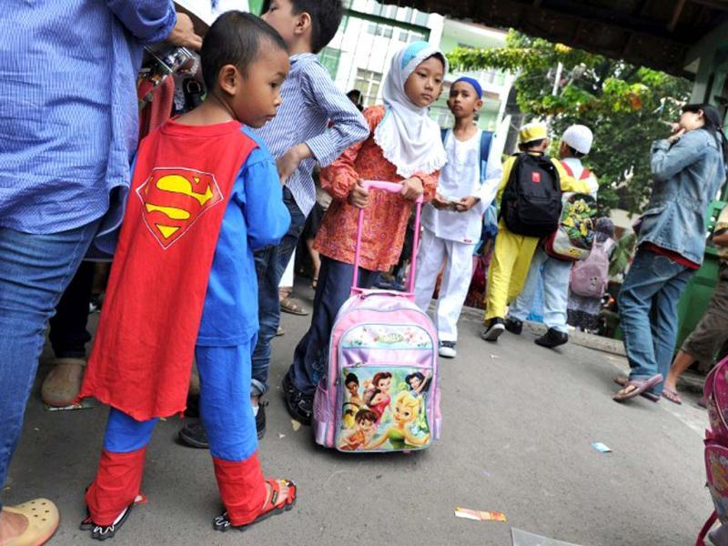 Four year old Ridwan (L) wearing Superman costume waits for his brother while public elementery school students leave school at the end of their classes in Jakarta. AFP photo
