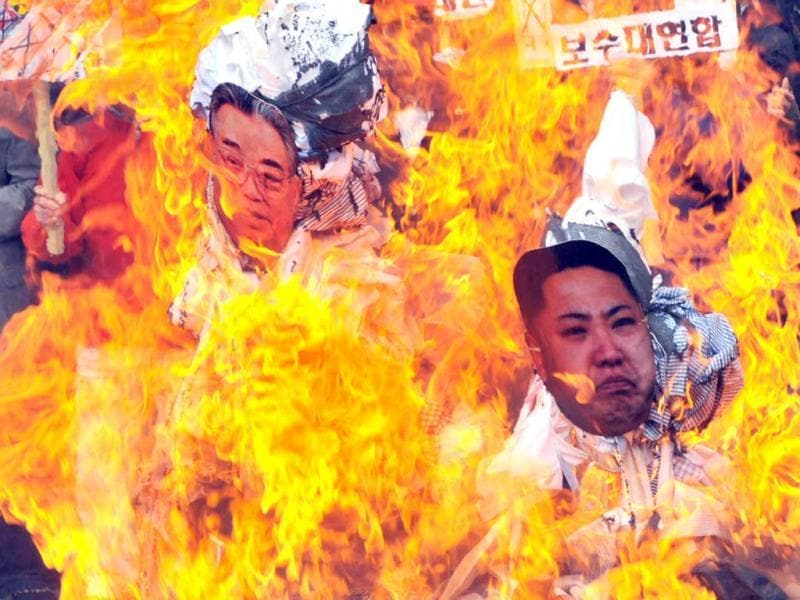 Dozens of South Korean activists burn effigies with the portraits of North Korea's late president Kim Il-Sung and his grandson and current leader Kim Jong-Un as they shout