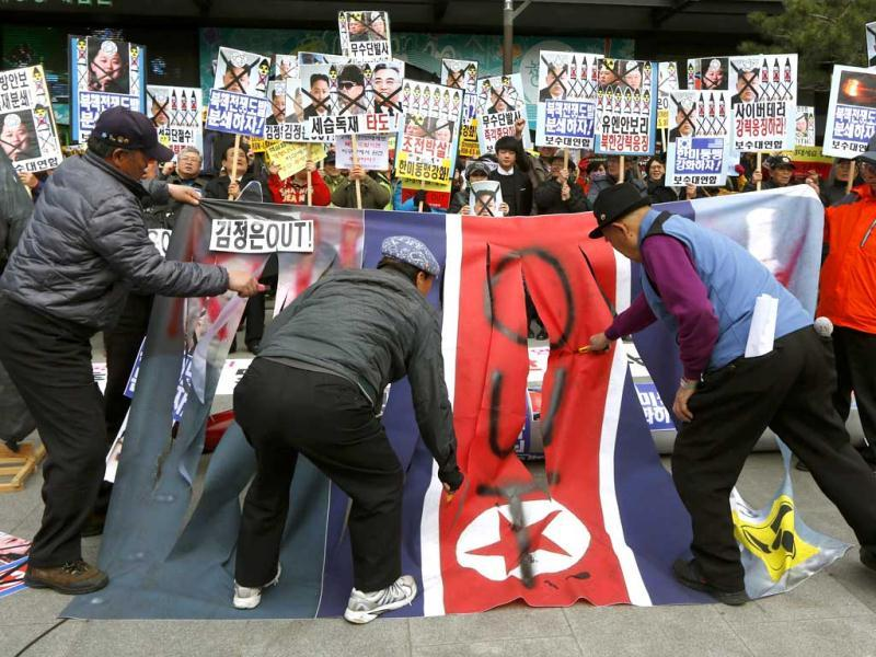 South Korean protesters deface a North Korean flag at an anti-North Korea protest on the birthday of late leader Kim Il Sung in Seoul, South Korea. The sign on the flag reads