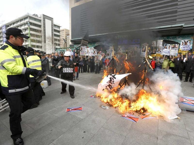 A police officer tries to extinguish a fire as South Korean protesters burn effigies of North Korean leader Kim Jong-Un, and late leaders Kim Jong Il and Kim Il Sung at an anti-North Korea protest on the birthday of Kim Il Sung in Seoul, South Korea. South Korea's defense minister, Kim Kwan-jin, told a parliamentary committee in Seoul on Monday that North Korea remains ready to launch a missile from its east coast, though he declined to disclose how he got the information. (AP)