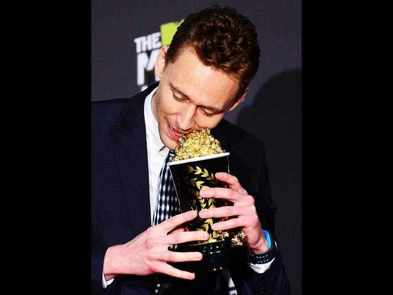 Tom Hiddlestone perhaps trying to eat the popcorn from his trophy as he poses in the press room during the 2013 MTV Movie Awards in Los Angeles, California, on April 14, 2013. (AFP Photo)