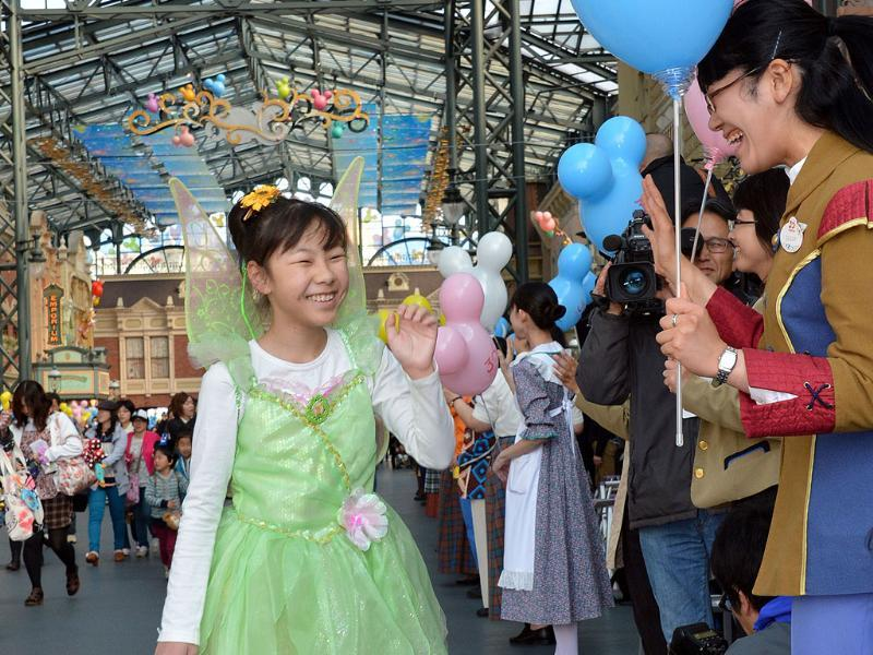 A girl in costume of Tinkerbell is greeted by casts of the Tokyo Disneyland as the Disney theme park celebrate its 30th anniversary in Tokyo. AFP photo