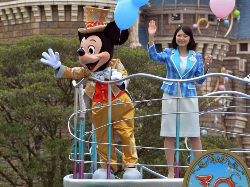 Mickey Mouse and Disney Resort Disney ambassador Ayaka Nagai wave their hands from a float for the parade as the Tokyo Disneyland celebrates its 30th anniversary in Tokyo. AFP