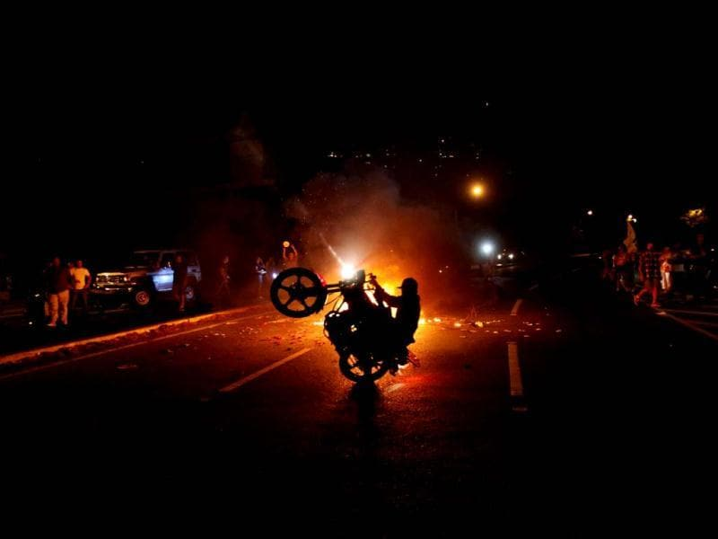 An opposition supporter does a wheelie on his motorcycle as others bang pots during a protest against interim President Nicolas Maduro in Caracas. (AP)
