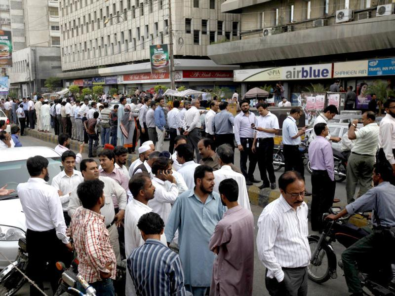 People stand outside their office buildings following an earthquake tremor in Karachi. An 8.0 magnitude earthquake struck Iran on Tuesday with tremors felt across Pakistan and India among other regions. Reuters