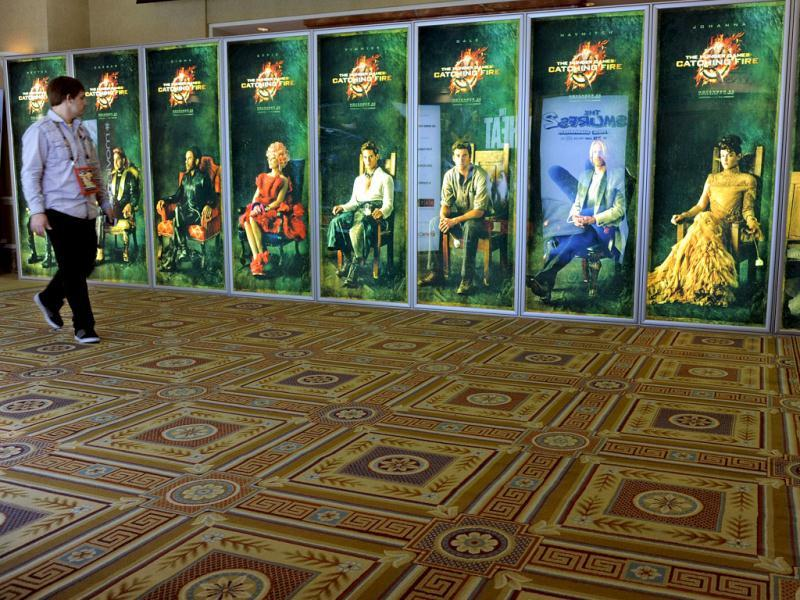 A CinemaCon attendee walks past a bank of posters for the upcoming film The Hunger Games: Catching Fire, during CinemaCon 2013 at Caesars Palace in Las Vegas. (AP)