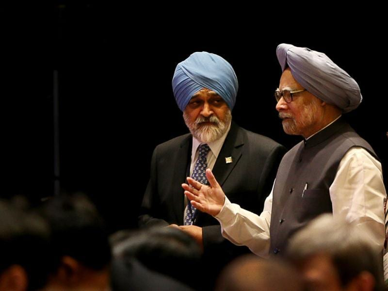 Prime Minister Manmohan Singh, right, speaks with Deputy Chairman of the Planning Commission Montek Singh Ahluwalia as he arrives for the Clean Energy Ministerial in New Delhi. AP photo