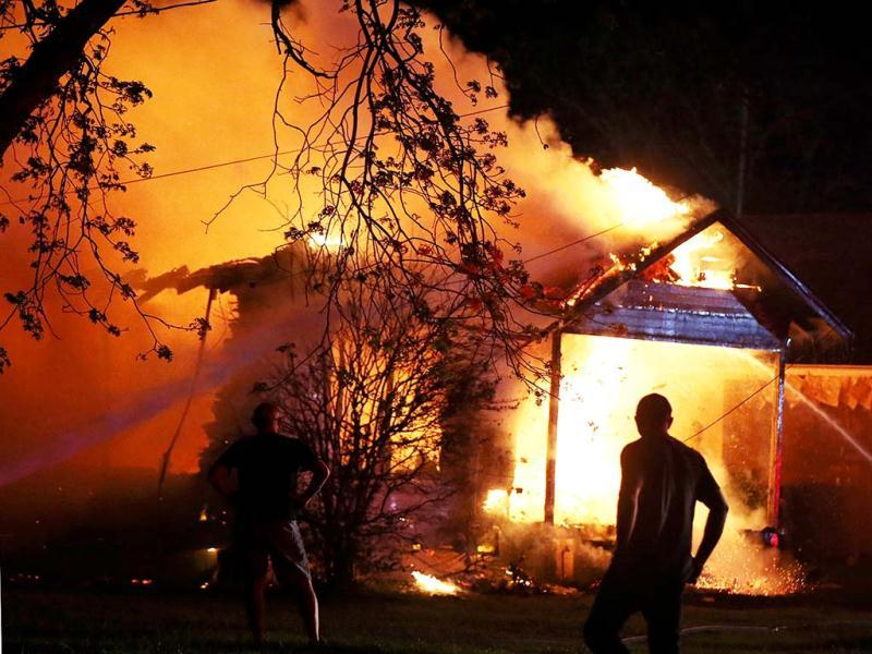 A person looks on as emergency workers fight a house fire after a near by fertilizer plant exploded in West, Texas. AP photo