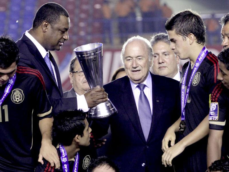 Jeffrey Webb, president of Concacaf holds the trophy as FIFA President Joseph Sepp Blatter gathers with Mexico's players after they won the Concacaf Under-17 men's soccer championship in Panama City. (AP)
