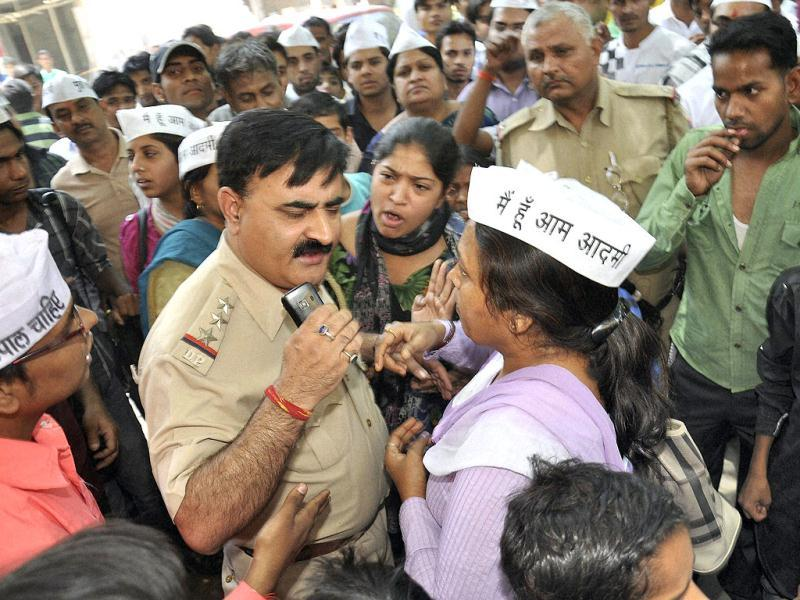 Police officer surrounded by AAP workers protesting against the brutal rape of a five-year-old girl in New Delhi. (PTI)
