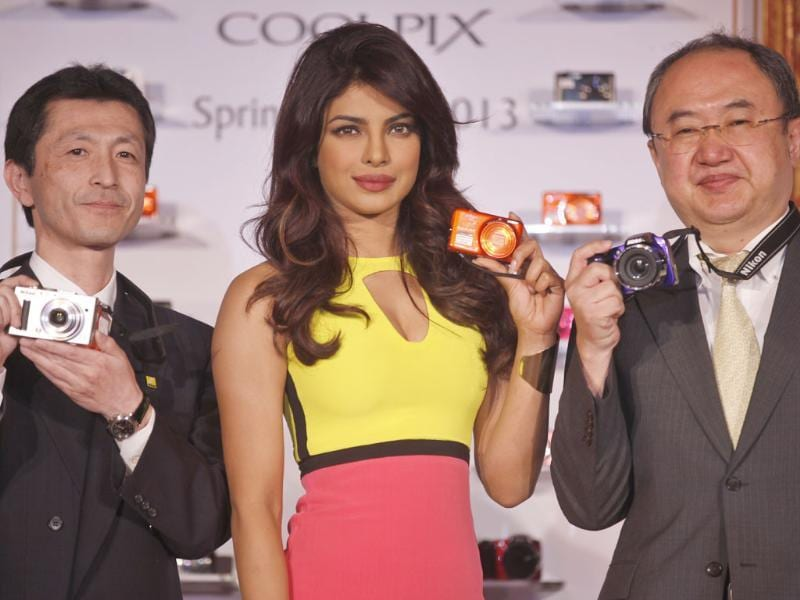 Bollywood actress Priyanka Chopra (C) poses with the new range of Nikon's Coolpix camera along with the Managing Director of Nikon India, Hiroshi Takashina (R), and the General Manager of the Communications Department, Tetsuya Morimoto (L) in New Delhi. Photo: Raj K Raj /Hindustan Times