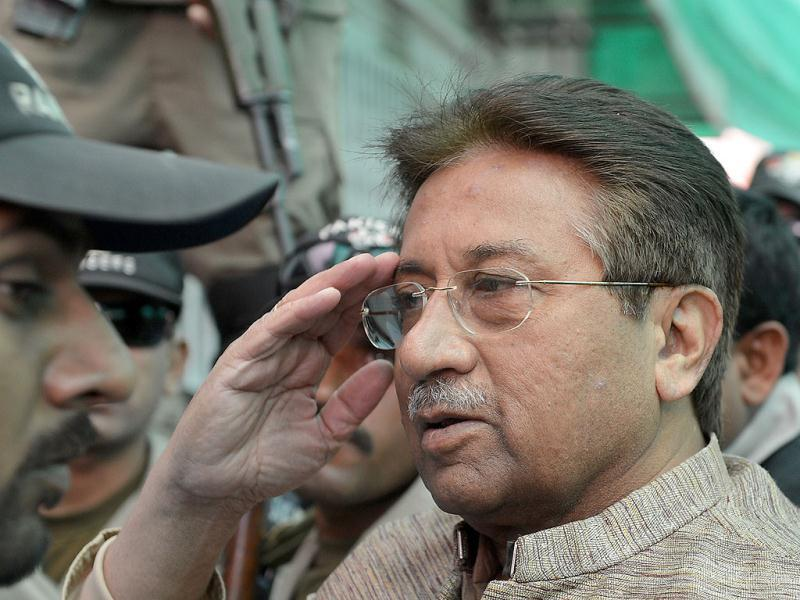 Former Pakistani president Pervez Musharraf is escorted by soldiers as he salutes on his arrival at an anti-terrorism court in Islamabad. (AFP)