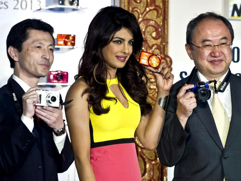 Priyanka Chopra (C) poses with the new range of Nikon's Coolpix camera along with the Managing Director of Nikon India, Hiroshi Takashina (R), and the General Manager of the Communications Department, Tetsuya Morimoto (L) in New Delhi. Photo: AFP/ Prakash Singh
