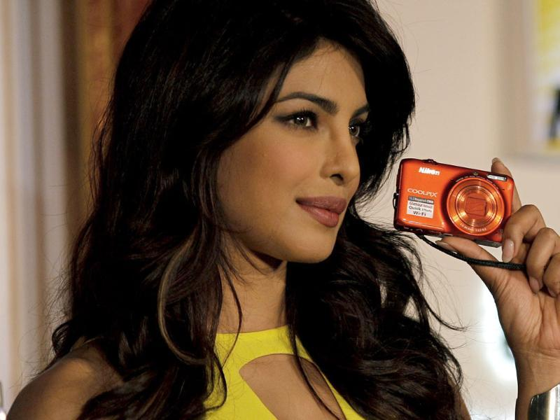 Priyanka Chopra poses with the new range of Nikon's Coolpix camera during its launch in New Delhi. Photo: AP/Altaf Qadri