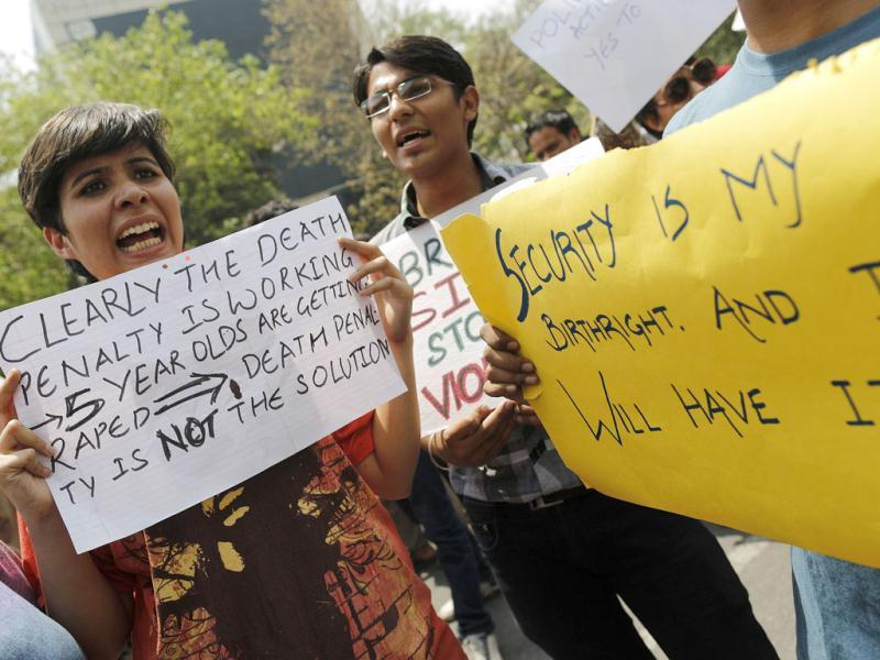 Demonstrators hold placards as they shout slogans during a protest outside police headquarters in New Delhi. Reuters