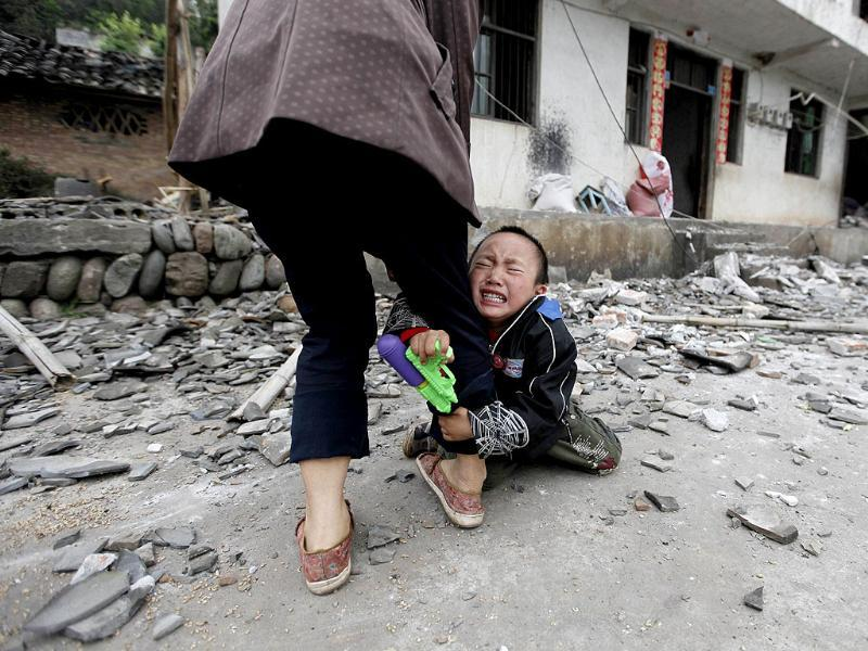 A boy holds his mother's leg as he cries in front of their damaged house after a strong 6.6 magnitude earthquake at Longmen village, Lushan county in Ya'an, Sichuan provinc, in China. Reuters