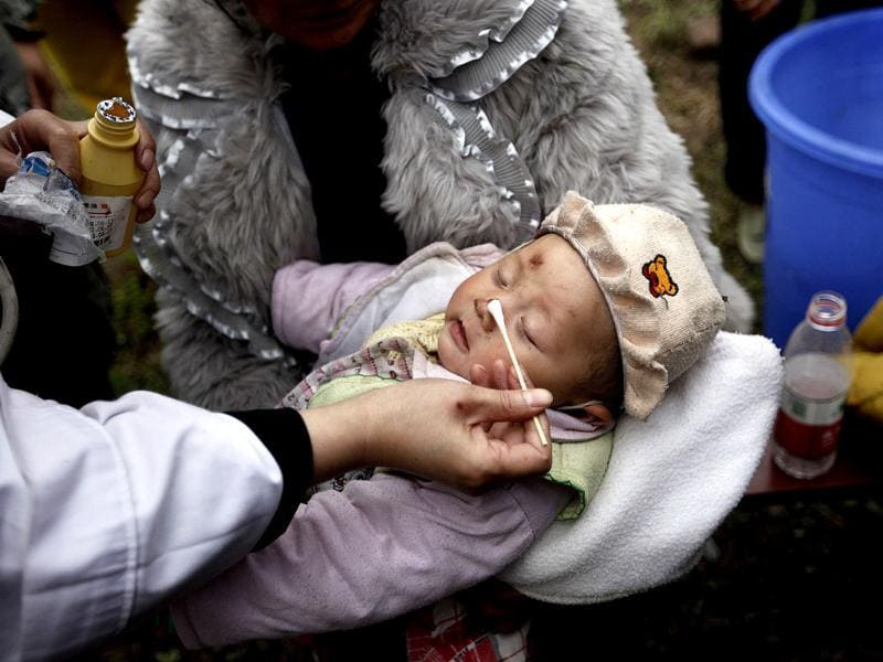 A three-month-old baby, whose mother was killed in a strong 6.6 magnitude earthquake, receives treatment at a medical point in Lushan county of Ya'an, Sichuan province in China. Reuters