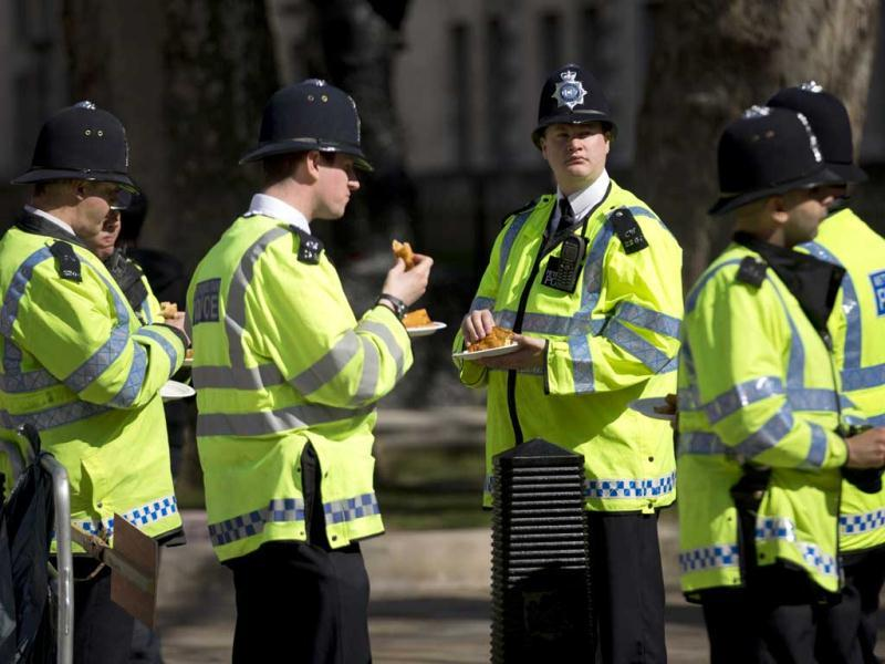 British police officers grab a bite near the route of the London Marathon. The London Marathon started in defiant mood on a glorious sunny morning Sunday despite concerns raised by the bomb attacks on the Boston Marathon six days ago. London's is the first major international marathon since the double bomb attack near the finish line in Boston, which left three people dead and more than 170 injured, including many who are still hospitalized. AP Photo