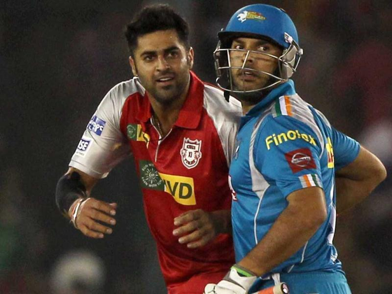 Kings XI Punjab's M S Gony, left, and Pune Warriors' Yuvraj Singh during the T20 League match at PCA Stadium in Mohali. PTI