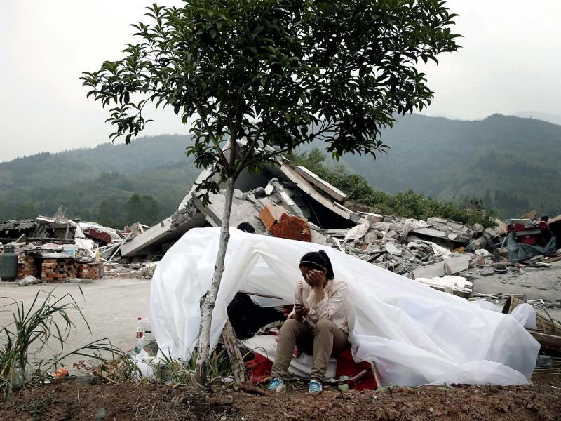 A child sits at a makeshift tent in front of homes destroyed by Saturday's earthquake in Longmen village in Lushan county of southwest China's Sichuan province. (AP)
